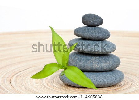 Stone tower on a wooden board with green bamboo leaf - stock photo