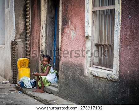 STONE TOWN, ZANZIBAR - AUGUST 31, 2014: A local girl sitting on stairs of one of the houses in the old town of Stone Town, Zanzibar, Tanzania. Horizontal orientation.