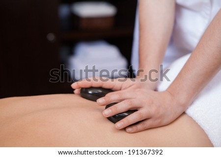 Stone treatment. Woman getting a hot stone massage at a day spa - stock photo
