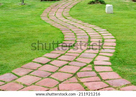 Stone walk path in the park with green grass - stock photo