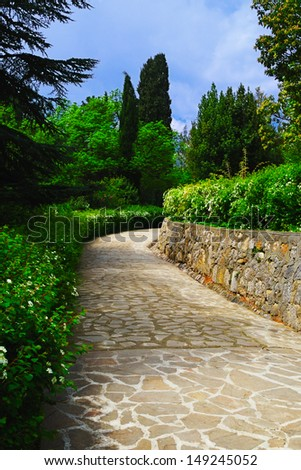 Stone walkway and a lush green vegetation in a Vorontsov park in the spring, Crimea - stock photo