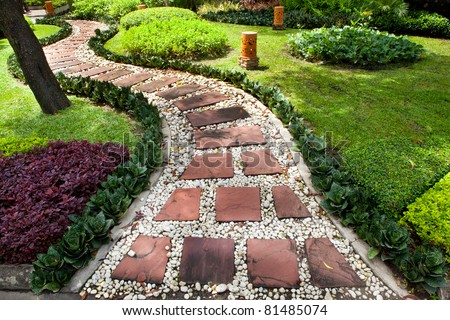 Stone walkway in the park with green grass - stock photo
