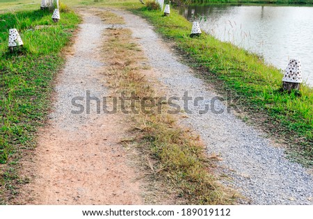 Stone walkway near the river in countryside village - stock photo