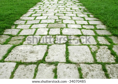 Stone walkway on a grassy field - stock photo