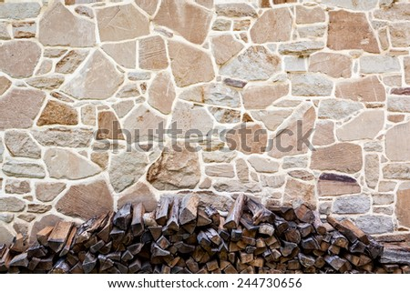 Stone Wall background texture with pile of logs - stock photo