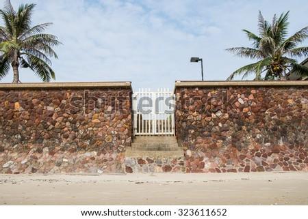 stone wall white door beach side sand - stock photo