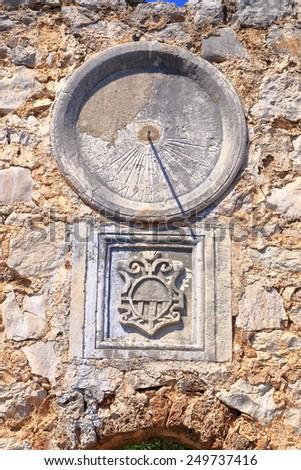 Stone wall with aged dial of a solar clock from the Dalmatian coast, Croatia - stock photo