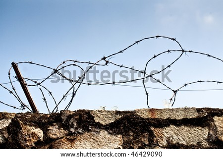 Stone wall with barbed wire against blue sky - stock photo
