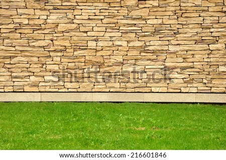 Stone wall with grass. Grass with brown brick wall background texture. - stock photo