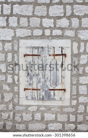 stone wall with wooden shutter window - stock photo