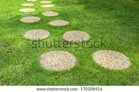 Stone wash pebble path on green grass  - stock photo