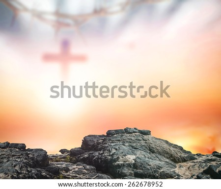 Stone with blurred crown of thorns and the cross on sunset background. - stock photo