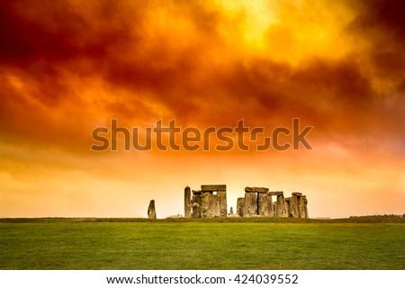 Stonehenge under stormy red orange and yellow sunset sky. - stock photo