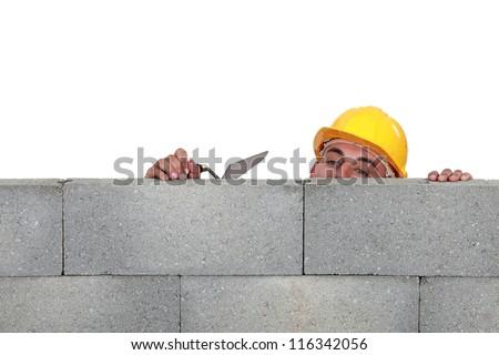 Stonemason peering over a low wall - stock photo