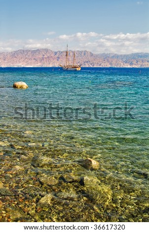 Stones and a sailing yacht in coastal waters of a resort Eilat in Israel - stock photo
