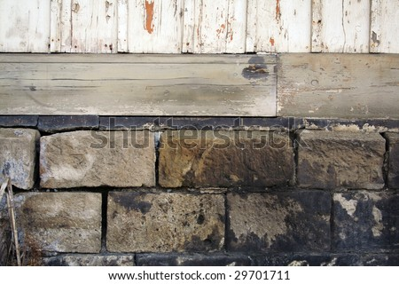 stones and foundation of an old wooden house - stock photo