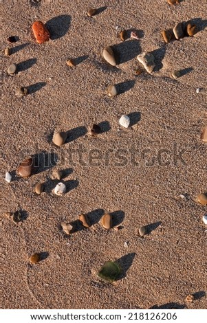 stones and sea worn shard of glass in bright late afternoon sun on a sandy beach  - stock photo
