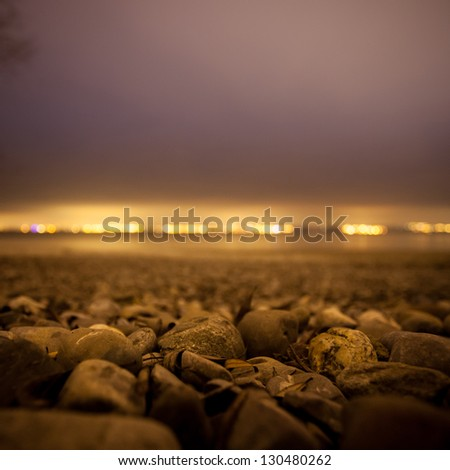 stones at lake constance beach at night - stock photo