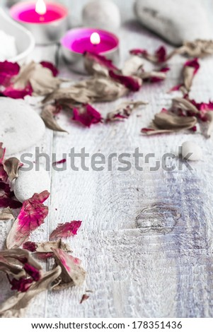 Stones, candles and petals of the rose on wooden background - stock photo