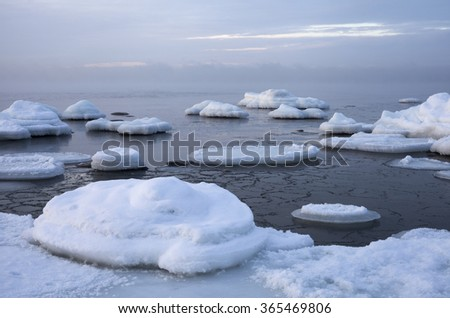 Stones covered with ice and snow at seaside on freezing cold winter day. Photographed at the coast of the Baltic Sea. - stock photo