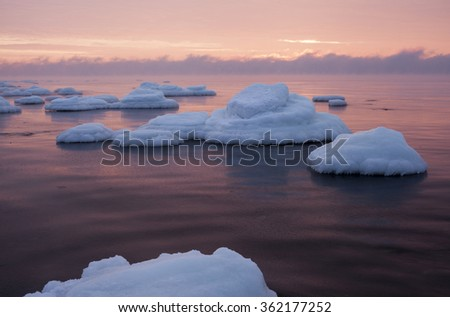 Stones covered with white ice caps in still sea at sunset at the coast Baltic Sea.  - stock photo