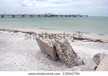 Stones from an old port, in the sand, with a large dock in the background, at the beach, Fort De Soto, Florida. - stock photo