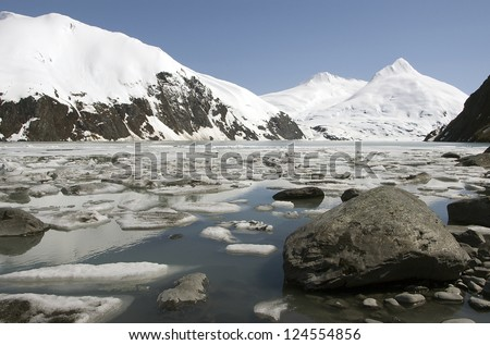Stones, ice and snow capped mountains near alaskan Portage glacier - stock photo