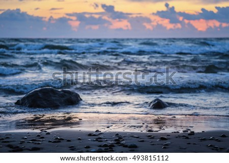 Stones in waves, sunset evening