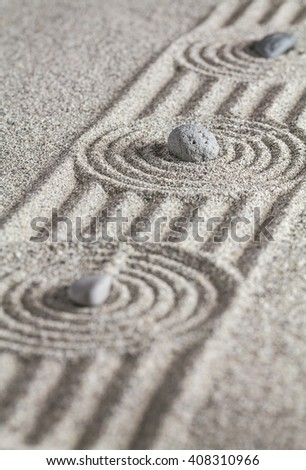 Stones of different colors and circles in the sand.