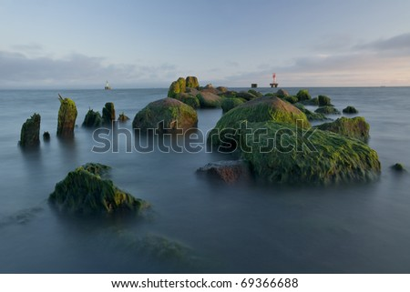 stones of the old pier on the beach with a lighthouse in the background - stock photo