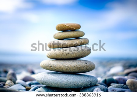 Stones pyramid on pebble beach symbolizing stability, zen, harmony, balance. Shallow depth of field.