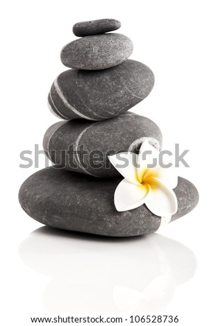 Stones pyramid with a plumeria flower, isolated on white background - stock photo
