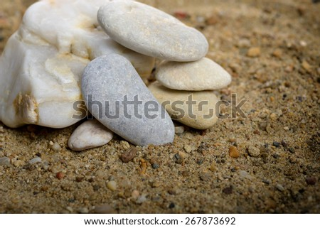 Stones stacked in sand background - stock photo