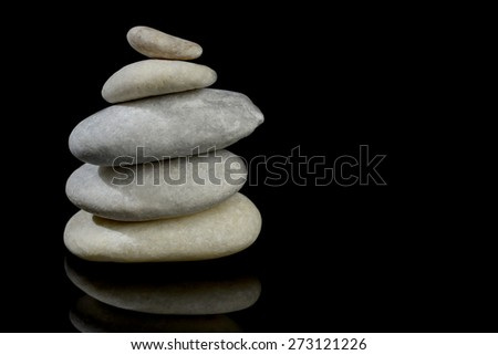 Stones stacked isolated black background with reflection - stock photo
