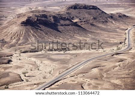 Stony desert landscapes with road and acacia trees, M'hamid, Sahara desert, Morocco. - stock photo
