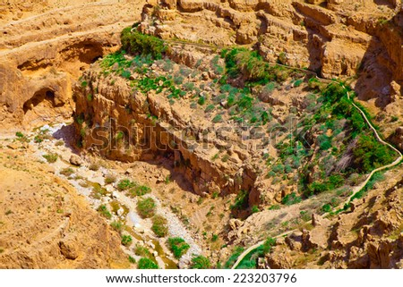 Stony desert valley with an ancient aqueduct and grass near it - stock photo