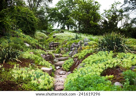 Stony path and stairs in the green blooming garden. - stock photo