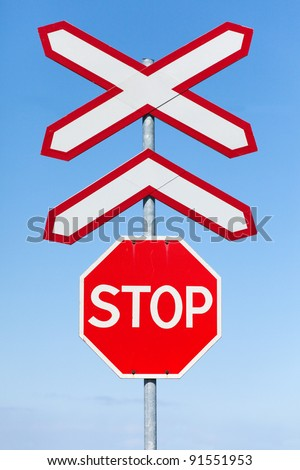Stop and Railway crossing signs over blue sky background - stock photo