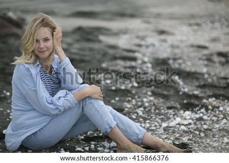 """stop and rest. The ease of mind. Woman enjoying the sea breeze , sea and sand . Smiles , do not think of """"tomorrow"""" . - stock photo"""