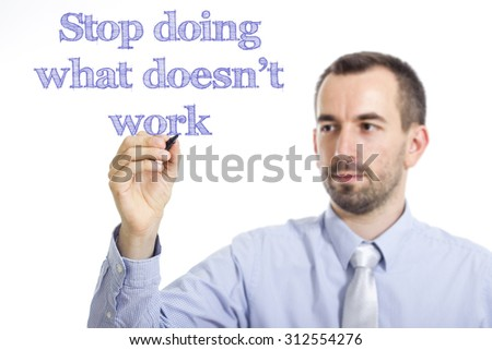Stop doing what doesn't work - Young businessman writing blue text on transparent surface