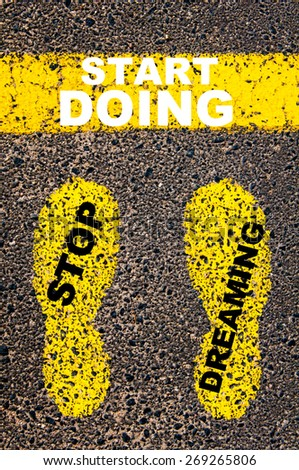Stop Dreaming Start Doing Message. Conceptual image with yellow paint footsteps on the road in front of horizontal line over asphalt stone background.  - stock photo
