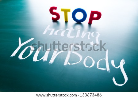 Stop hating your body concept, colorful words on blackboard - stock photo