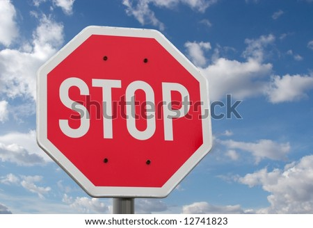 Stop sign against blue sky and clouds - stock photo