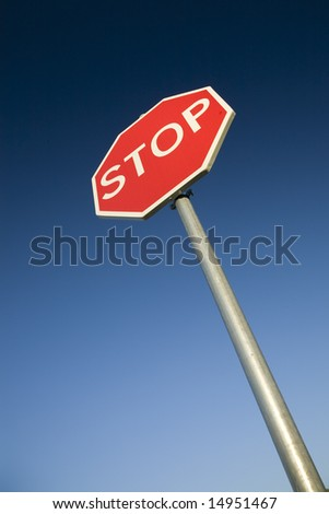 Stop sign against deep blue sky. - stock photo