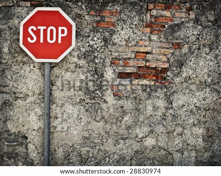 stop sign against grungy wall, may represent protection,dead end... - stock photo