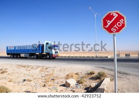 stop sign and truck on road - stock photo