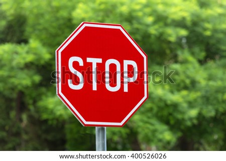 Stop sign closeup with woods in the background