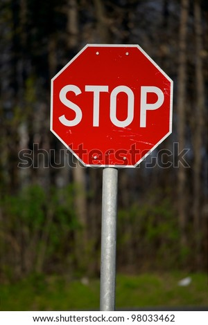 Stop sign closeup with woods in the background - stock photo