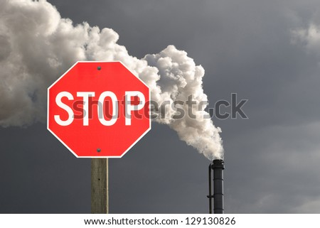 Stop sign in front of smokestack pollution with dark cloud in the background - stock photo