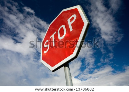 Stop sign with blue sky background - stock photo